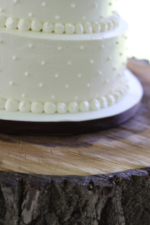 white swiss dot wedding cake on rustic wood cake stand | Tuxedo & Russell's Hudson Valley June Wedding | Brooklyn Homemaker